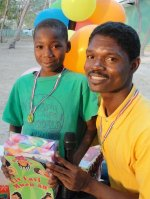 Seen here the Kids' EE Haiti Director Pastor Pierre Banes Laurore distributing the Make Jesus Smile shoeboxes. Used as the conduit to activate the child sponsorship program.