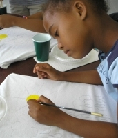 Seen below the children of Barbados hand-painting the Kisses from Heaven tee shirts