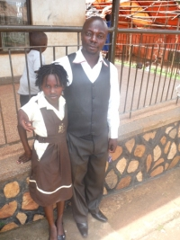 Daphine seen here with her new dad - Pastor Abraham on her first day at school - praise God.