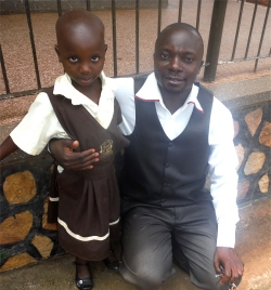 Charity seen here with her new dad - Pastor Abraham on her first day at school - praise God.