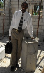 Seen here Pastor Rodrigues, trained by technitians at Clean Water for Haiti, standing beside the first filter produced in this small production plant.