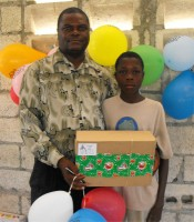 Seen here Pastor Anous Nordeus the founder of Maranatha Ministries distirbuting the Make Jesus Smile shoeboxes to the orphans.