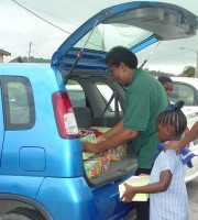 Paulette Scantlebury helping pack the boxes into the car ready for shipment