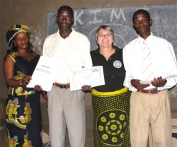 Patrick seen here receiving his certificate and KIMI manual and curriculum from Mama Pinos, (left) and Jenny. and Pastor Paul
