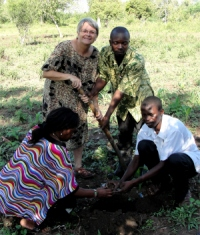 Seen here Jenny Tryhane, Founder of UCT (back left) with Pastor Abraham, the Uganda UCT Representative holding the hoe that was used to plant a memorial tree on the boundary of the land. In the front is Mama Pinos who officially handed the land over on behalf of her husband Bishop Pinos and right Pastor Paul who will be the resident Pastor of this project.