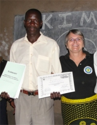 God raised up a teacher, Patrick, to assist Pastor Paul coordinate the KIMI program in this region, seen here with Jenny Tryhane his teacher presenting him with his KIMI curriculum.