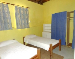 The leaders bedroom has two single beds, a waredrobe and chest of drawers